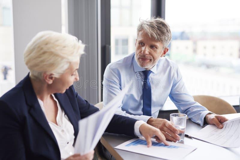 Geschäftspaare, welche die Diagramme analysieren stockfotos