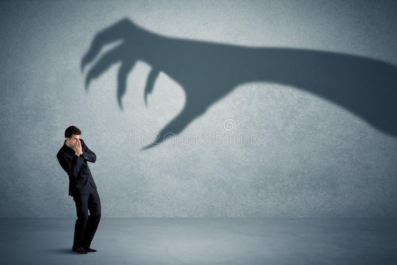 Geschäftsperson ängstlich von einem großen Monstergreifer-Schattenkonzept lizenzfreie stockfotografie