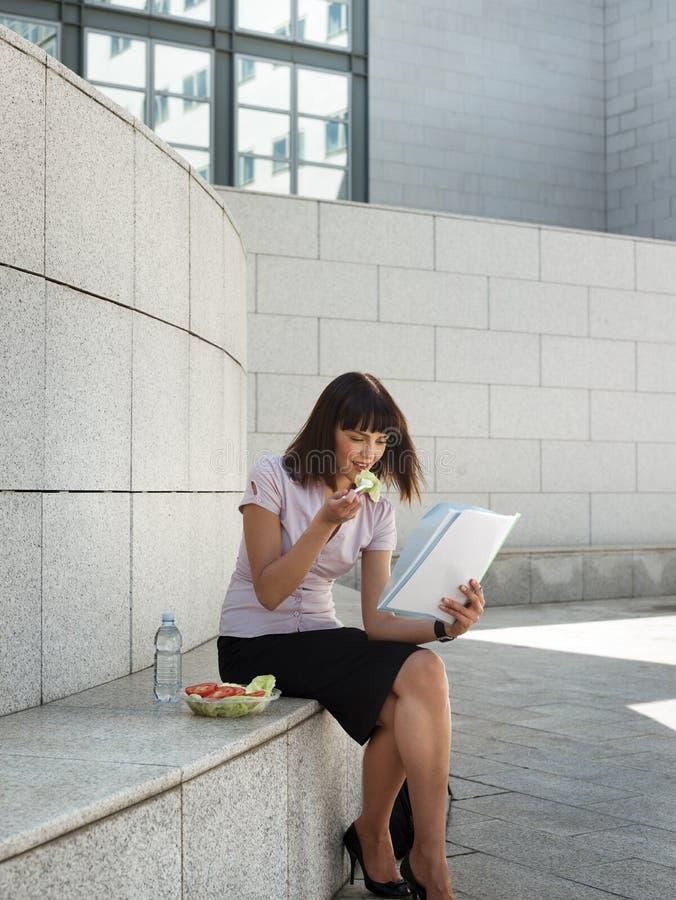 Geschäftsperson, die das Mittagessen außerhalb des Büros isst lizenzfreies stockbild