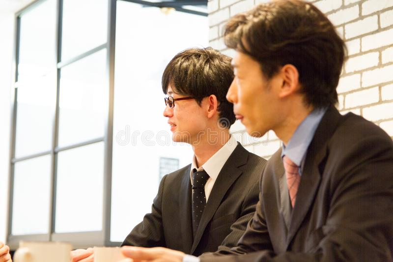 Geschäftsperson mit zwei Japanern, die an Teambesprechung teilnimmt lizenzfreie stockbilder