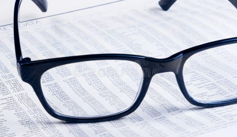 Geschäftssehen Finanzzeitungsbericht durch Glaslinse, Arbeitsplatz des Geschäftsmannes stockbild