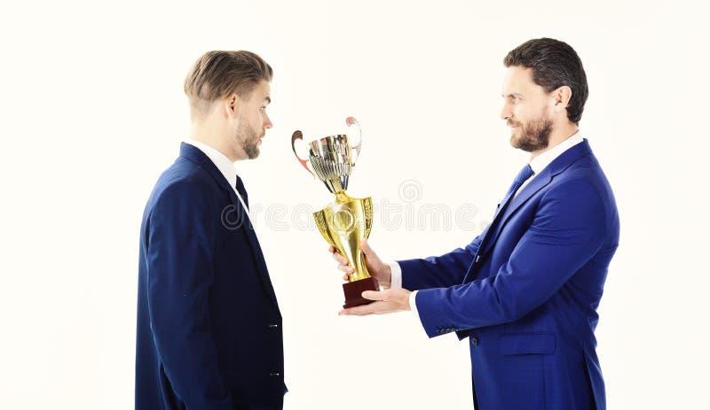 Geschäftssieg und Erfolgskonzept Geschäftsmann mit überraschtem Gesicht empfängt goldenen Preis Zugesprochene beste Arbeitskraft stockfoto