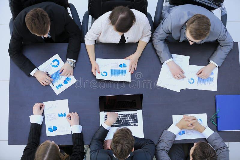 Geschäftsteam auf ein Seminar Finanzdiagramme der Co besprechend lizenzfreie stockfotos