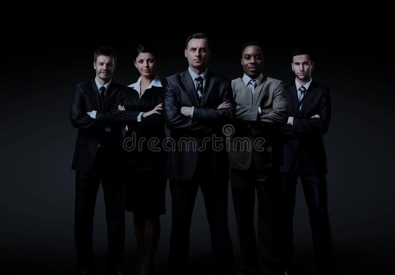 Geschäftsteam, das über einem dunklen Hintergrund steht stockfotografie