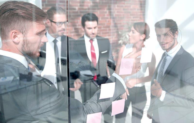 Geschäftsteam, das auf den Anmerkungen über das Glasbrett darstellt lizenzfreie stockfotografie