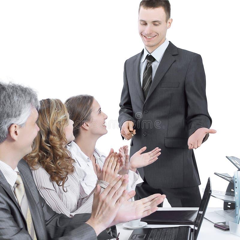 Geschäftsteam, das den Sprecher an einer Geschäftsdarstellung applaudiert lizenzfreie stockbilder