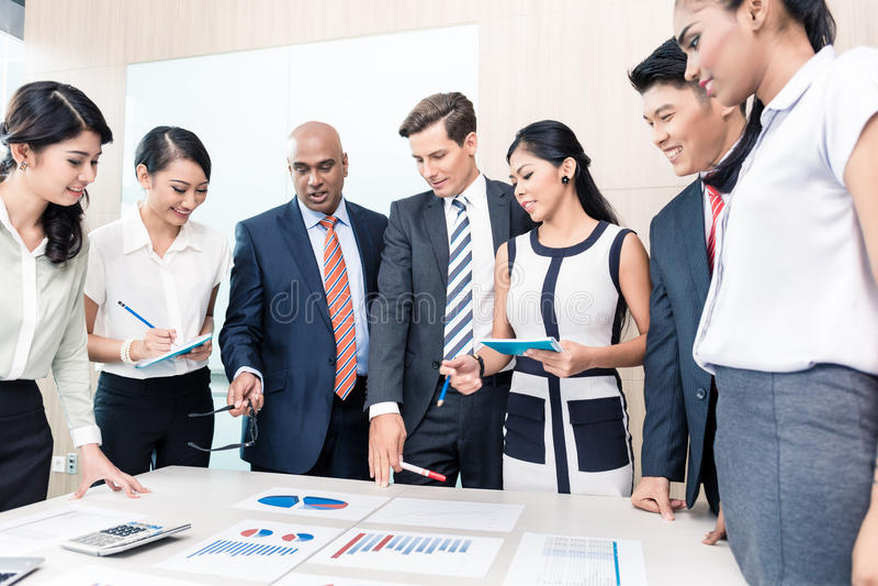 Geschäftsteam, das Diagramme und Zahlen in der Sitzung bespricht lizenzfreie stockfotografie