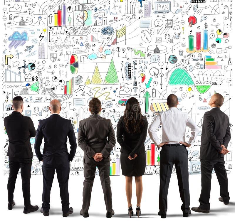 Geschäftsteam, das ein neues komplexes Projekt zeichnet stockbild