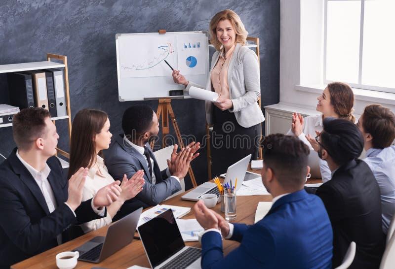 Geschäftsteam, das erfolgreichen weiblichen Manager bei der Sitzung beglückwünscht lizenzfreies stockbild