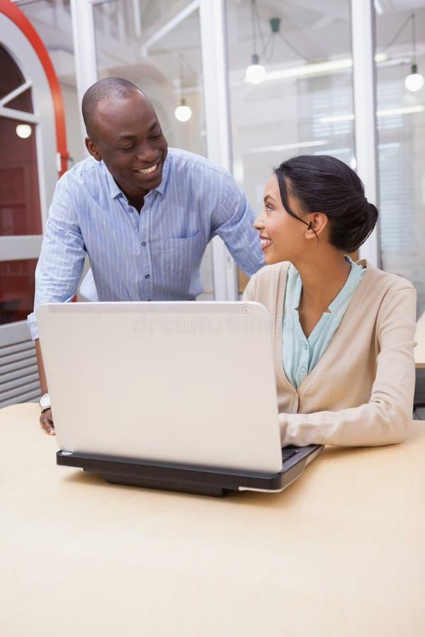 Geschäftsteam, das glücklich zusammen an Laptop arbeitet lizenzfreie stockfotos