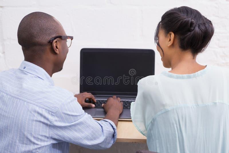 Geschäftsteam, das glücklich zusammen an Laptop arbeitet stockfotos