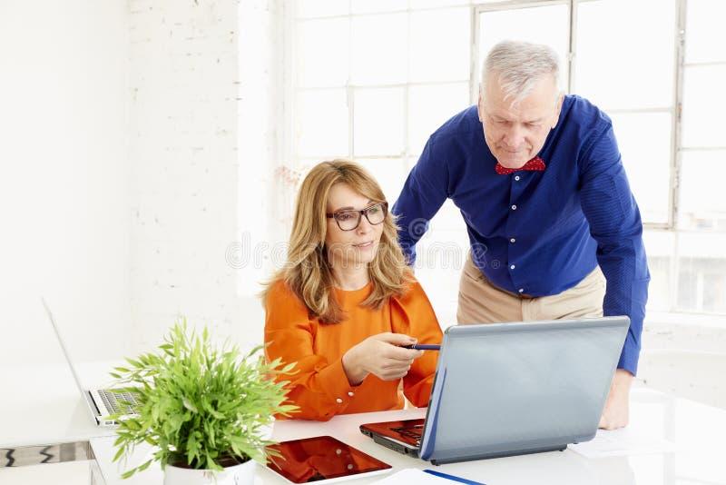 Geschäftsteam, das im Büro zusammenarbeitet Mittlere gealterte Geschäftsfrau und älterer Geschäftsmann, die an neuem Projekt arbe stockfoto