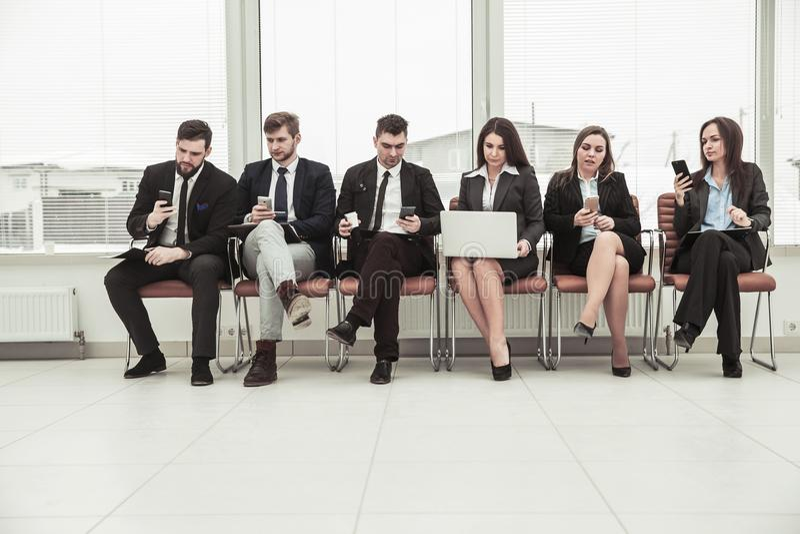 Geschäftsteam, das im Internet nach Informationen unter Verwendung eines Smartphone und eines Laptops sitzen in der Lobby vom mod lizenzfreies stockbild