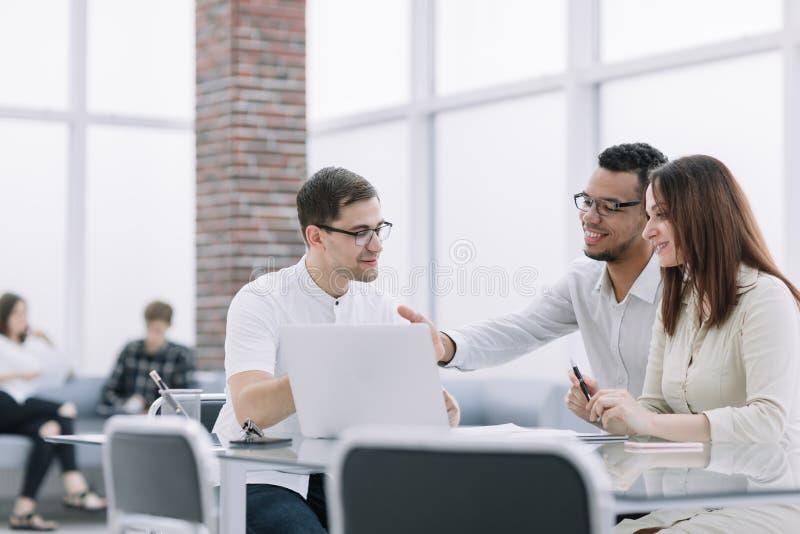 Geschäftsteam, das on-line-Informationen bei der Arbeitssitzung bespricht stockfotografie