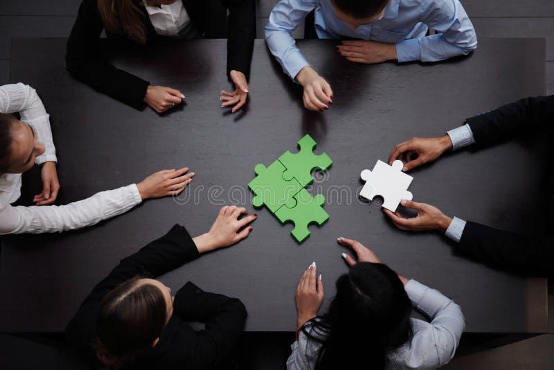 Geschäftsteam, das Puzzlespiel löst stockfoto
