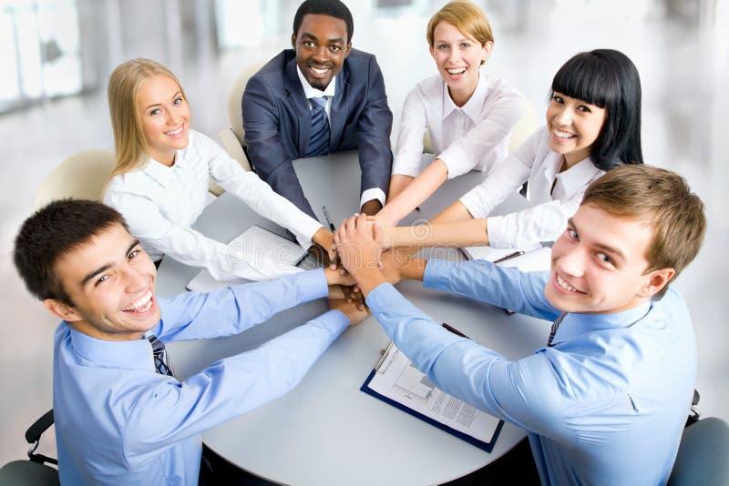 Geschäftsteam, das Stapel von den Händen auf Arbeitsplatz macht lizenzfreies stockbild