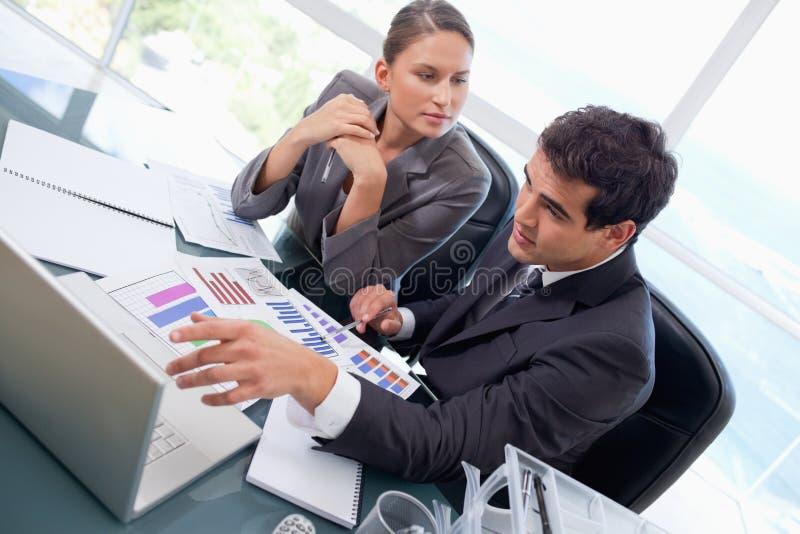 Geschäftsteam, das Statistiken mit einem Laptop studiert stockbild