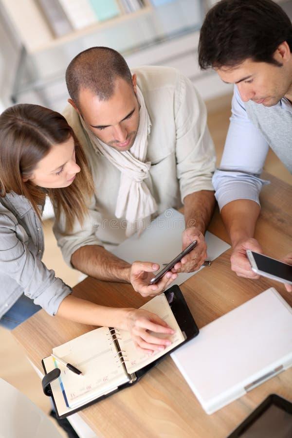 Geschäftsteam, das unter Verwendung der digitalen Geräte arbeitet lizenzfreies stockbild