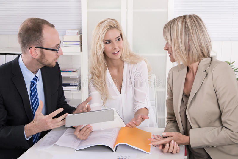 Geschäftsteam des Mannes und der Frau, die um Schreibtisch in einer Sitzung sitzen lizenzfreie stockbilder