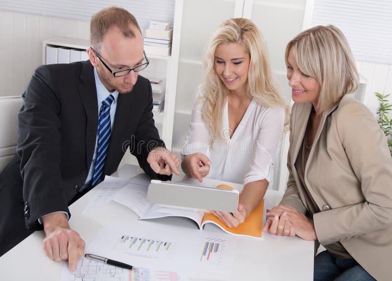 Geschäftsteam des Mannes und der Frau, die um Schreibtisch in einer Sitzung sitzen lizenzfreie stockfotos