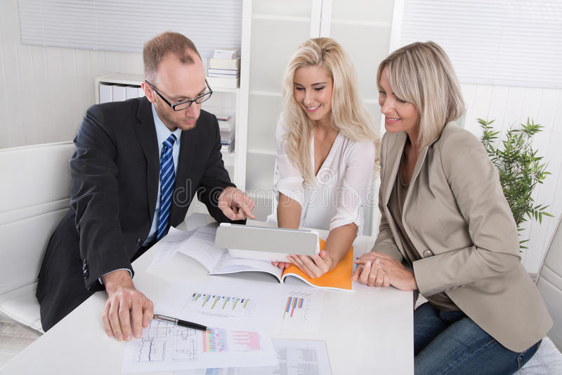 Geschäftsteam des Mannes und der Frau, die um Schreibtisch in einer Sitzung sitzen lizenzfreies stockbild