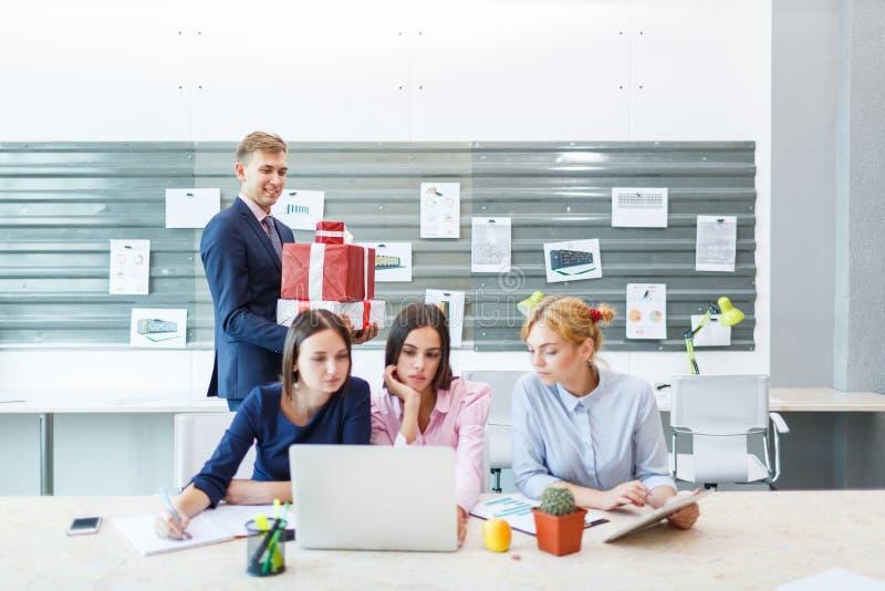 Geschäftsteam in einem modernen hellen Büroinnenraum bei der Arbeit über einen Laptop stockfotografie