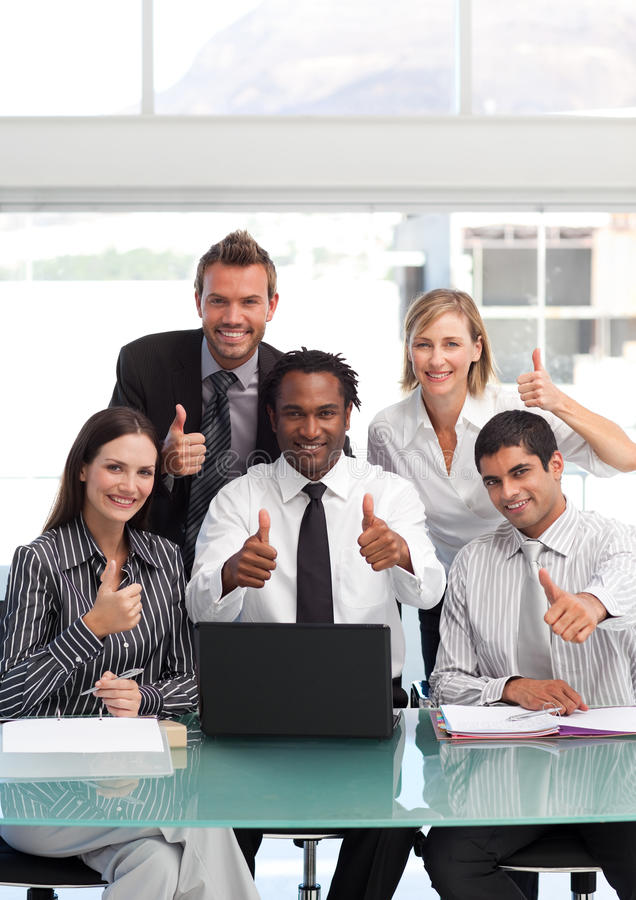 Geschäftsteam mit den Daumen oben lächelnd an der Kamera stockfotografie