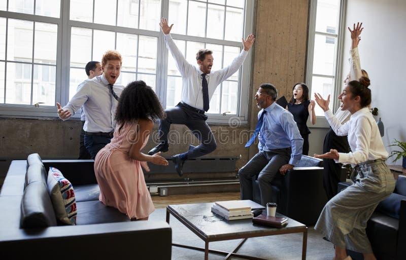 Geschäftsteam springen für Freude am Schlagen des Ziels in der Sitzung lizenzfreie stockbilder