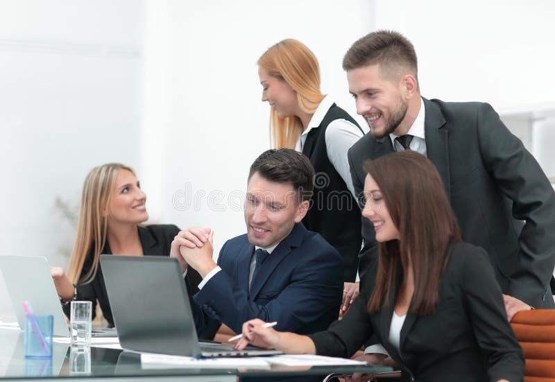 Geschäftsteam, welches die neuen Informationen, stehend vor dem offenen Laptop bespricht lizenzfreie stockbilder