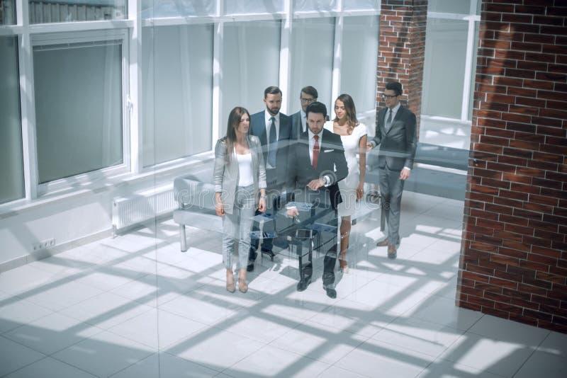 Geschäftsteam, Wirtschaftler gruppieren das Gehen am modernen hellen Büroinnenraum stockfoto