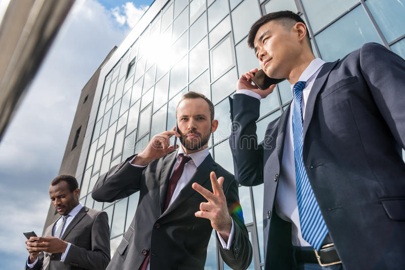 Geschäftsteambesprechung und mit Smartphones draußen nahe Bürogebäude lizenzfreie stockfotografie