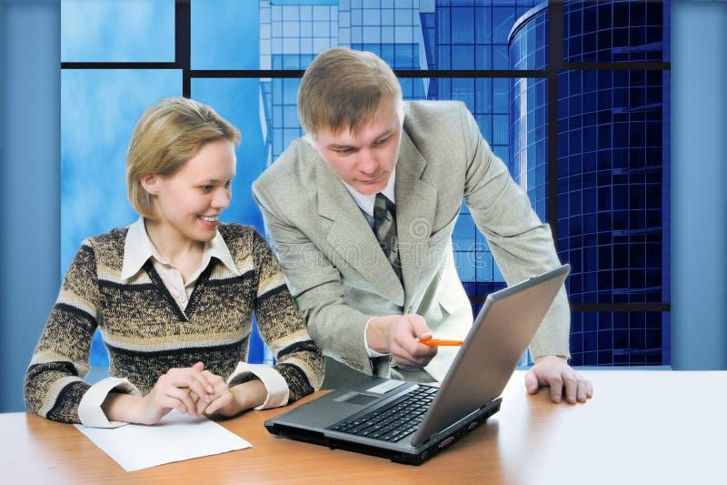 Geschäftsteammann und -frau arbeiten im Büro auf Laptop mit Ansichtgeschäftsgebäuden stockbild