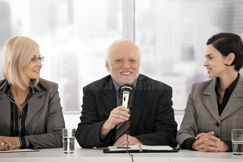 Geschäftstreffen, älterer Mann mit Mikrofon lizenzfreie stockfotografie