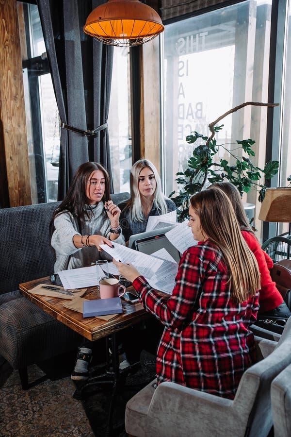 Geschäftstreffen in einem Café, vier junge Frauen, die an einem Tisch sitzen und Dokumente besprechen lizenzfreies stockfoto