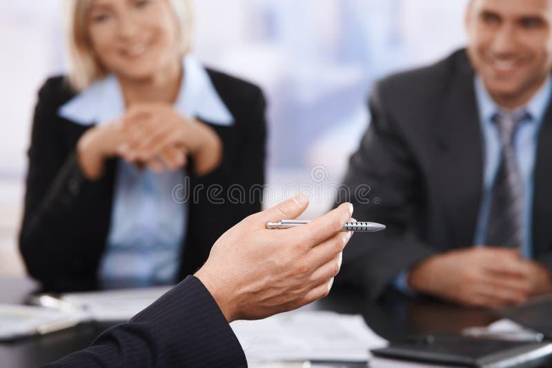 Geschäftstreffen, Hand mit Feder in der Nahaufnahme lizenzfreie stockfotografie