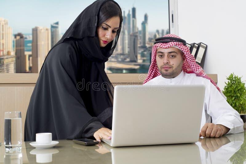 Geschäftstreffen im Büro, im arabischen Geschäftsmann u. arabischer Sekretär in tragendem hijab, das an Laptop arbeitet lizenzfreie stockfotos