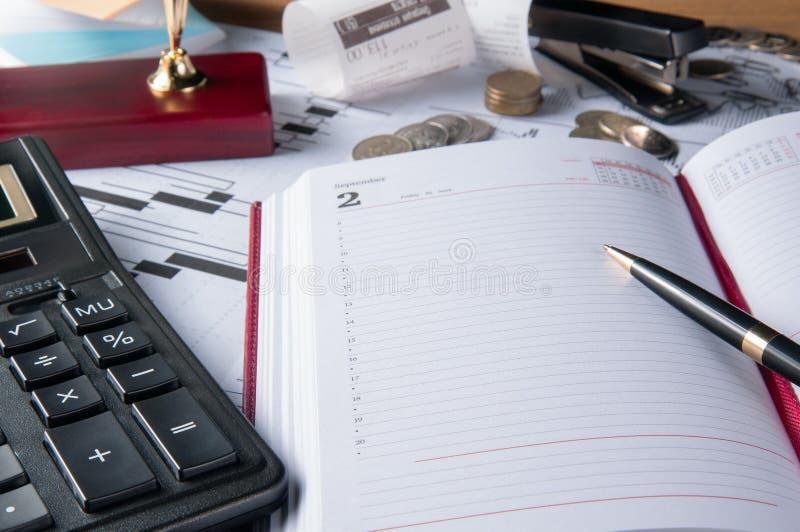 Geschäftszubehör Notizbuch, Taschenrechner, Füllfederhalter und Grafiken, Tabellen, Diagramme auf einem hölzernen Schreibtisch lizenzfreies stockbild