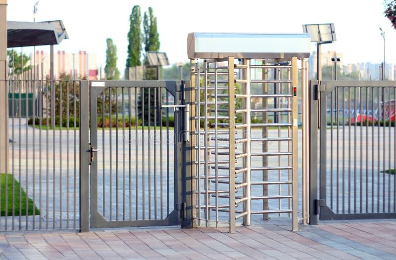 Geschütztes Eingangstor Eingang zum B?ro durch gro?es in den vollen menschlichen Wachstumsedelstahldrehkreuzen Konzept der Sicher stockfoto