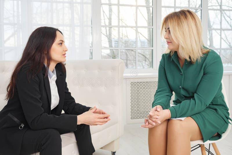 Gesch?ftsfrau, die auf der Couch spricht mit weiblichem Psychologen sitzt stockbilder
