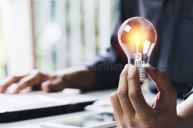 Gesch?ftsfrau, die Gl?hlampe auf dem Schreibtisch im B?ro h?lt und Computer in Finanz, erkl?rend, Energie, Ideenkonzept verwendet lizenzfreies stockbild