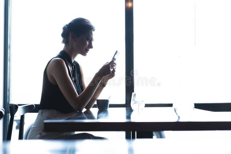 Gesch?ftsfrau, die Smartphone w?hrend des Mittagessens im Caf? verwendet lizenzfreies stockbild