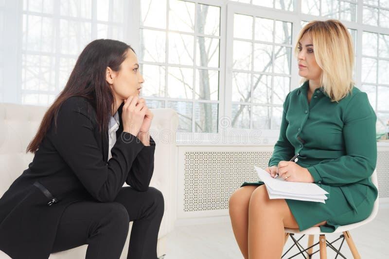 Gesch?ftsfrau mit Nervenzusammenbruch spricht mit dem Psychologen, der Kenntnisse nimmt lizenzfreie stockfotos
