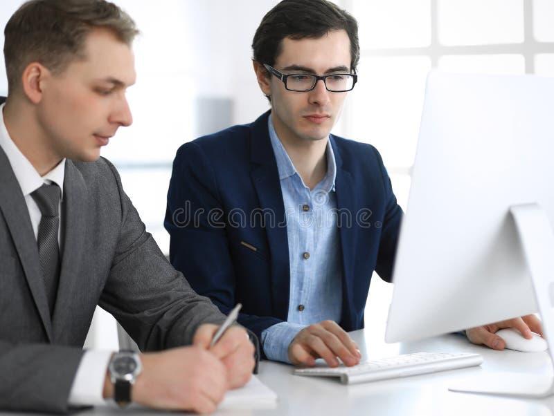 Gesch?ftsm?nner, die mit Computer im modernen B?ro arbeiten Headshot des m?nnlichen Unternehmers oder des Unternehmensmanagers am stockfotos