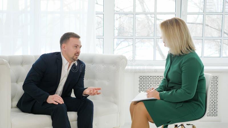 Gesch?ftsmann, der auf der Couch spricht mit weiblichem Psychologen sitzt stockfotografie