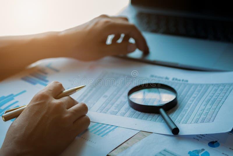 Gesch?ftsmann, der durch eine Lupe zu den Dokumenten schaut Betriebswirtschaftliche Auswertung und Rechnungspr?fung Lupe auf eine lizenzfreies stockfoto