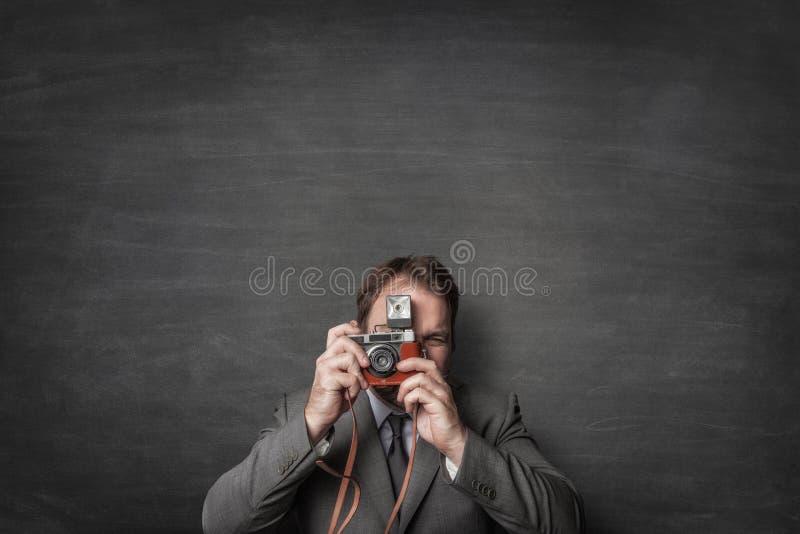 Gesch?ftsmann, der ein Foto mit alter Weinlesekamera macht lizenzfreie stockbilder