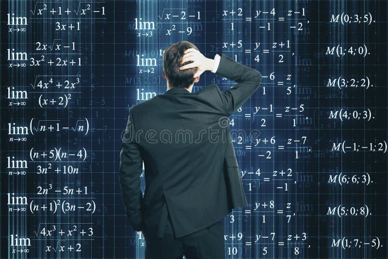 Gesch?ftsmann, der Formeln betrachtet lizenzfreie stockbilder