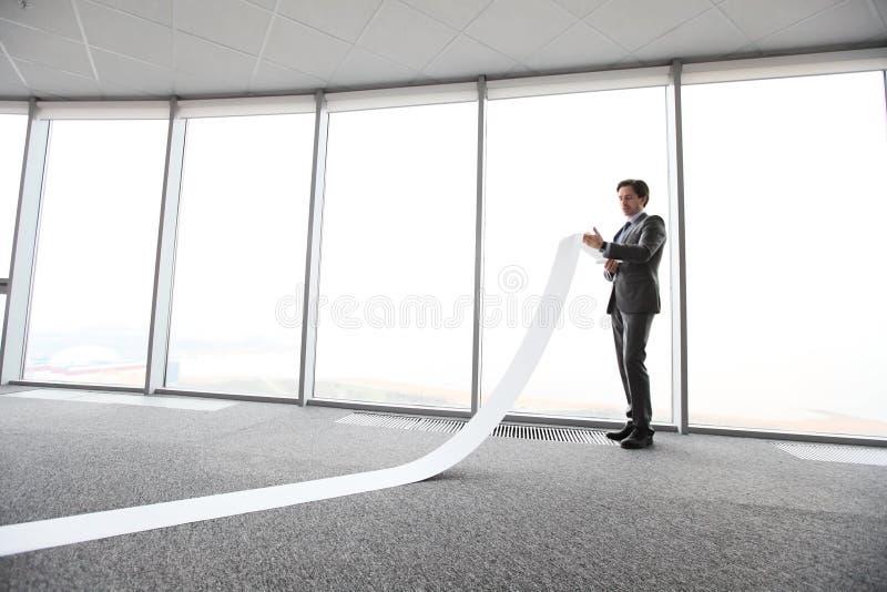 Gesch?ftsmann, der lange Papierliste liest stockbilder
