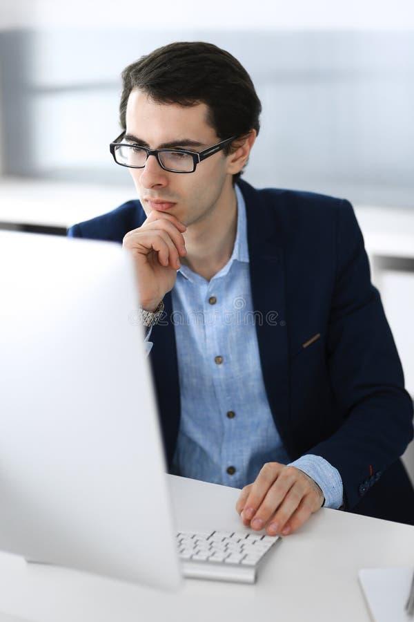 Gesch?ftsmann, der mit Computer im modernen B?ro arbeitet Headshot des m?nnlichen Unternehmers oder des Unternehmensmanagers am A lizenzfreies stockbild