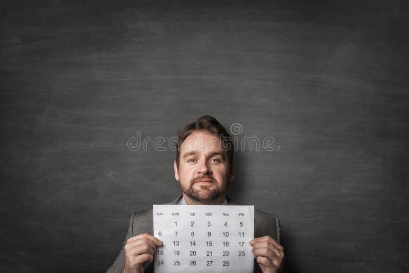 Gesch?ftsmann, der Papier calendard vor ihm zeigt stockbild